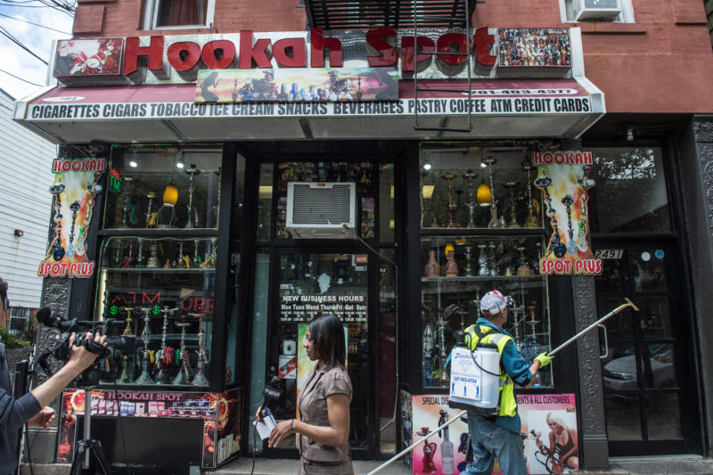 The scene outside the Hookah Spot in the Bronx on May 24, 2014, nearly one week after 14-year-old Javier Payne was allegedly pushed through the storefront glass window while in custody of the NYPD. A window washer cleaned the windows of the shop. (Robert Stolarik for JJIE)