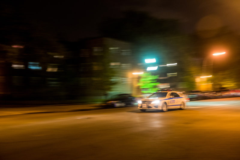 A police car flew past the Edenwald Houses in the North Bronx on May 17 2014. (Robert Stolarik for JJIE)