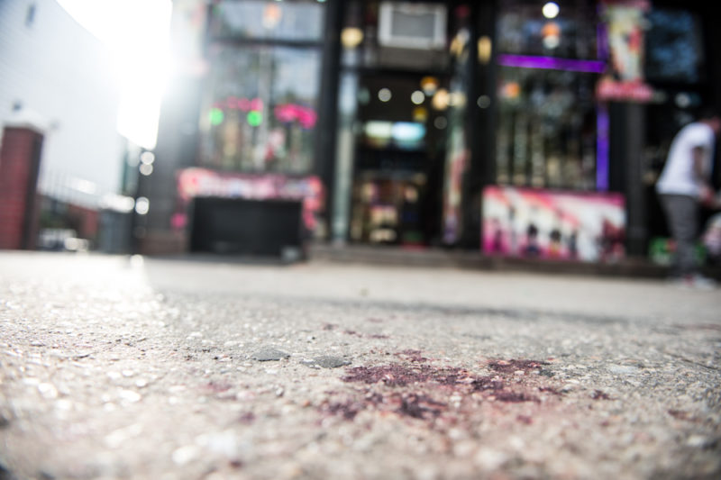 The blood stained sidewalk on May 18, 2014 outside the Hookah Spot on Arthur Avenue in the Bronx where 14-year-old Javier Payne was allegedly pushed through a glass window by police from the 45th precinct while he was handcuffed. (Robert Stolarik for JJIE)