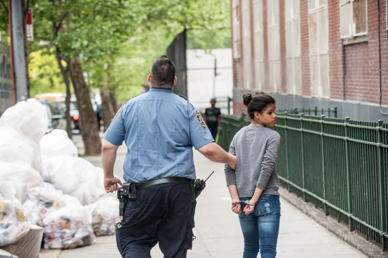A young girl is handcuffed and place under arrest on May 21, 2014 outside Public School 22 Wednesday afternoon in the Bronx where Javier Payne attends the 8th grade. (Robert Stolarik for JJIE)