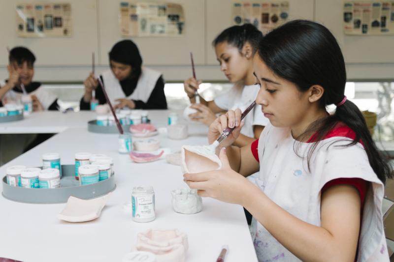 Art school Inner City Arts: Students sit at tables and paint glaze on handmade pieces in one of two ceramics studios.