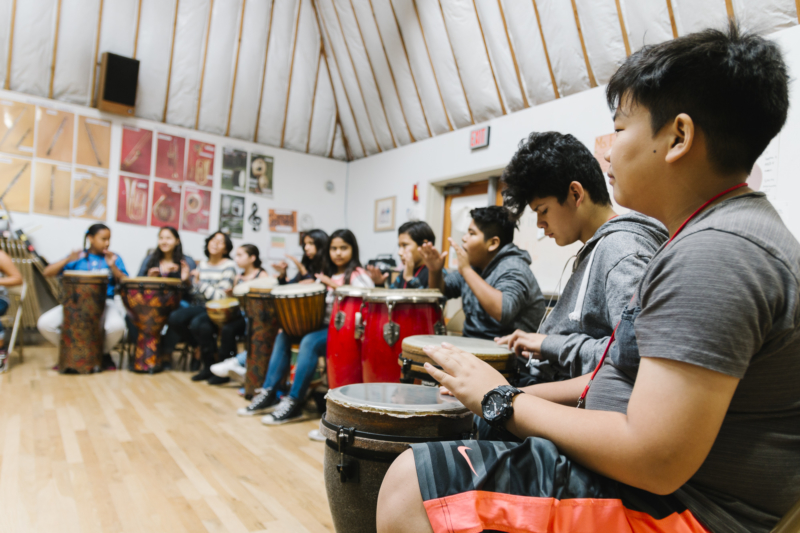 Art school Inner City Arts: Students sitting in a large circle play drums as a group inside a music studio at Inner-City Arts.