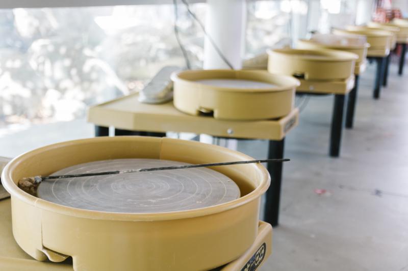 Art school Inner City Arts: Eight pottery wheels line a glass window.