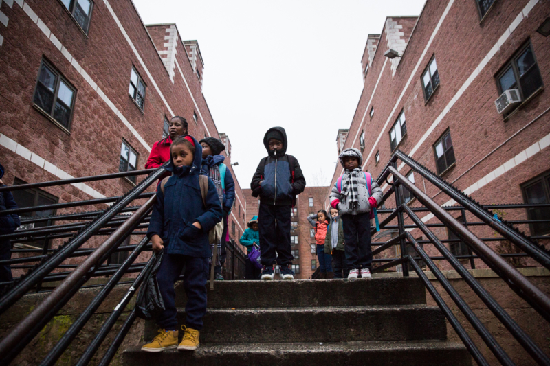 Chronic School Absenteeism: Primary school=age children in windter coats stand on steps to brick apartment complex walkway in the drizzling rain.