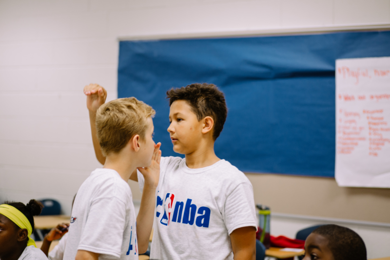 Youth in a NBA sponsored t-shirts discussing the answer.