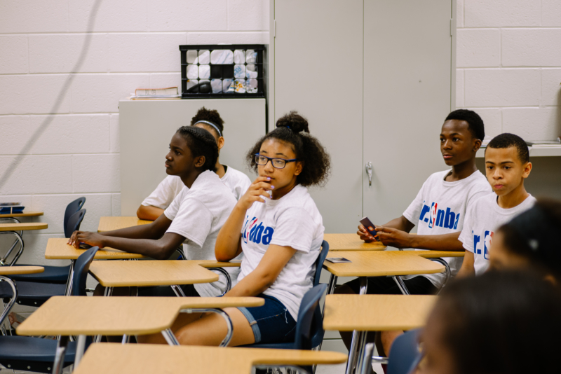 Youth in NBA sponsored t-shirts sitting in a classroom