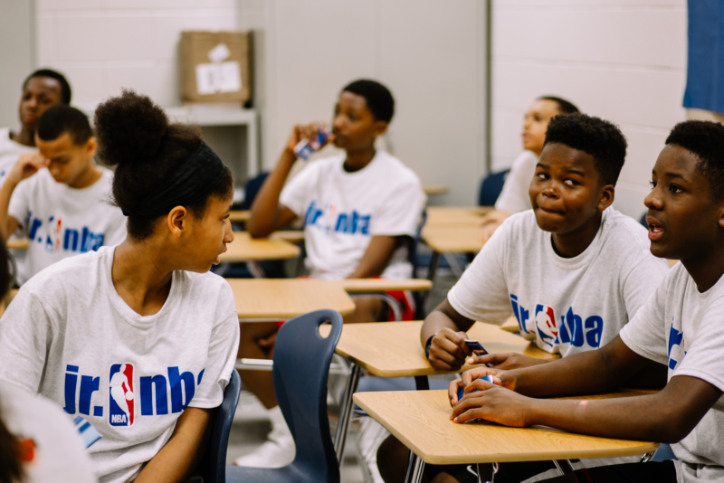 youth wearing NBA sponsored t-shirts sitting in a classroom