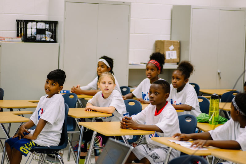 a group of youth sitting in a classroom.