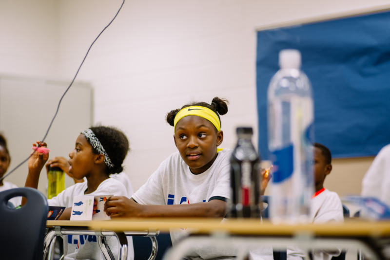A youth wearing a yellow Nike headband, sitting in a classroom with other youth.