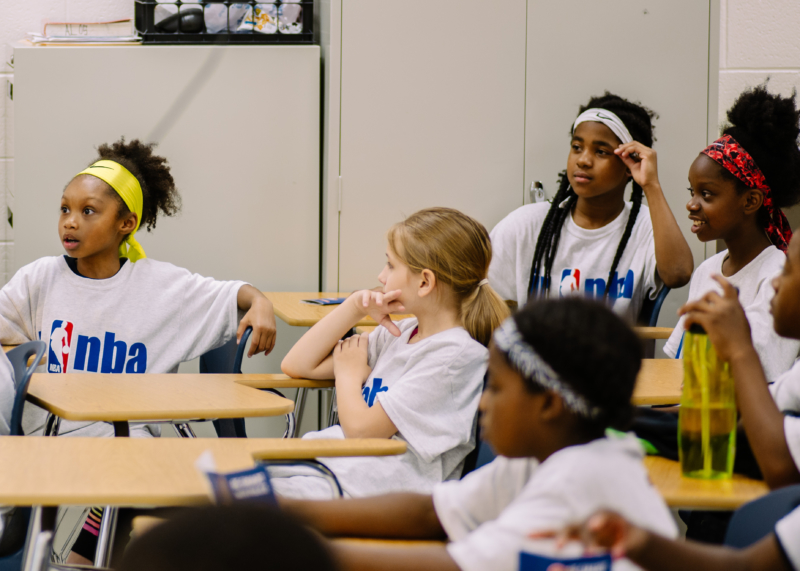 Students wearing NBA sponsored t-shirts sitting in a classroom thinking of what the best choice for the issue presented before them.