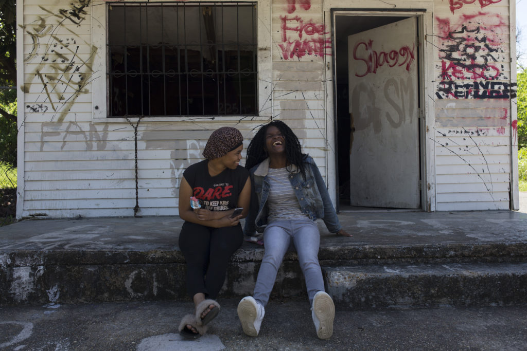 Teen Hangout Baton Rouge: Girls laughing while sitting on the front porch cement steps with graffiti on the walls behind them at the old abandoned while house.