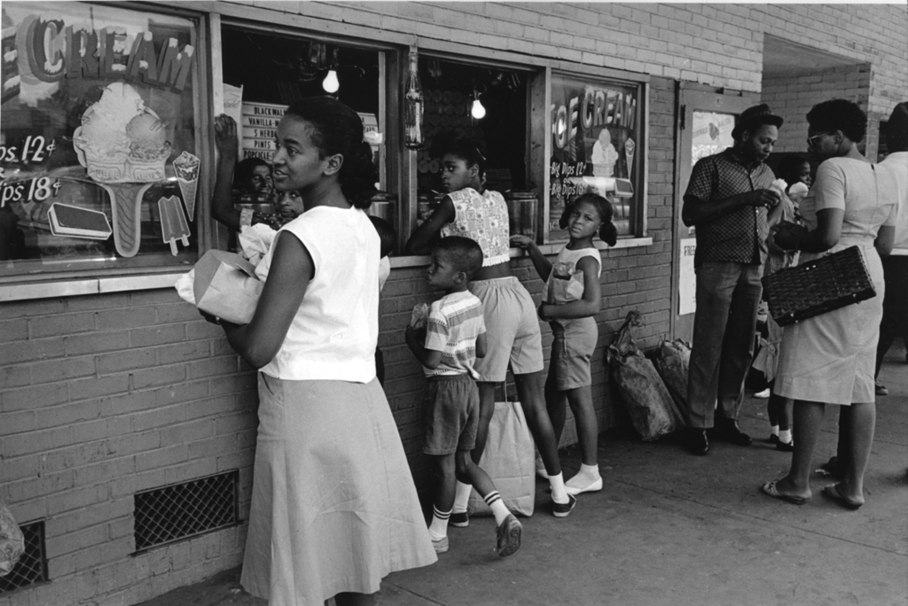 Families gathered at an ice cream shop with adults chatting and children waiting for their cones. Black & white photo from 1960s by Rusty Miller