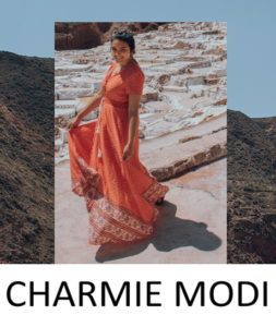 Young woman with dark hair, photographer Charmie Modi, standng on pale tan, arrid, on rocky terrain in deep orange sari.
