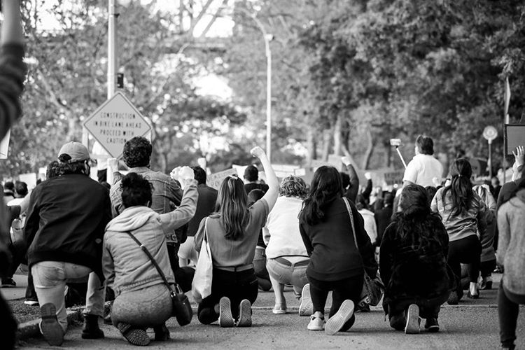 George Floyd Protest Astoria, New York park, black & white photo, looking at the backs of a large group of people kneeling on one knee with right fists raised