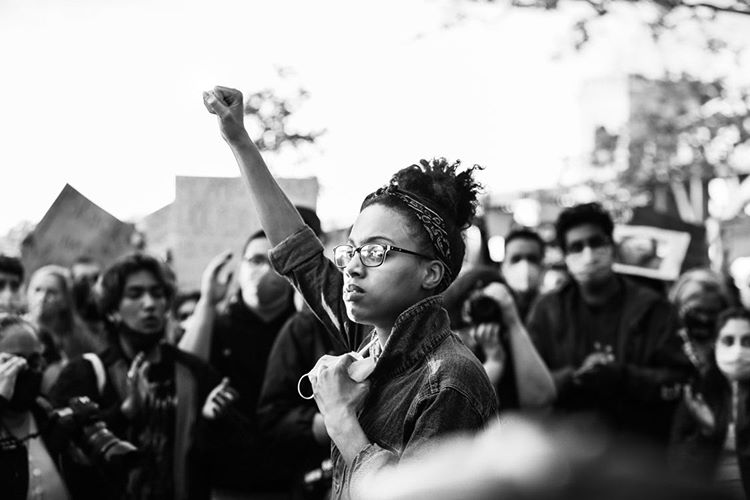 George Floyd Protest Astoria, New York park, black & white photo, closeup of young woman with black hair and glassesraising her right fist in protest