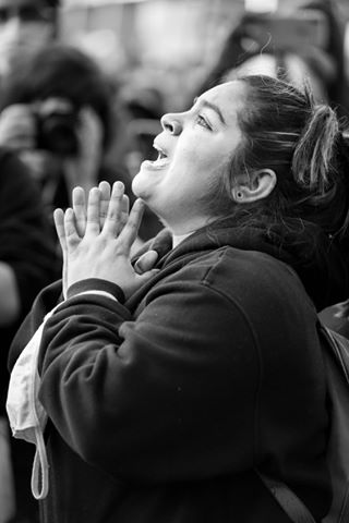 George Floyd Protest Astoria, New York park, black & white photo, closeup profile of young woman with short, dark hair wearing dark sweatshirt clasping hands and looking upward while chanting