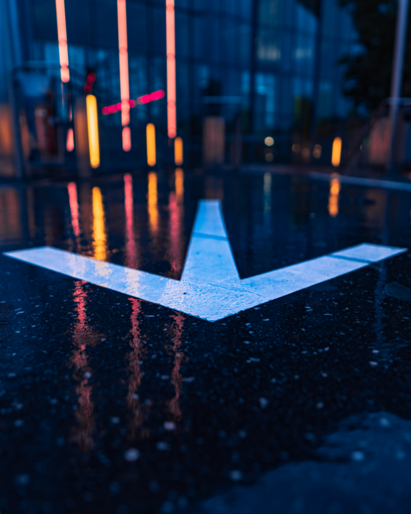 Bokeh photo at night of large white arrow painted on dark, wet asphalt street.
