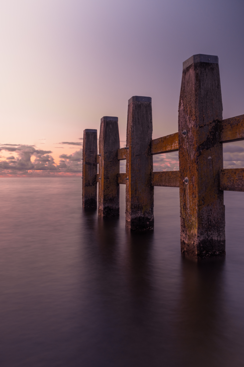Weathered wooden pier posts and cross supports stand in dark, calm water uner dusky skies.