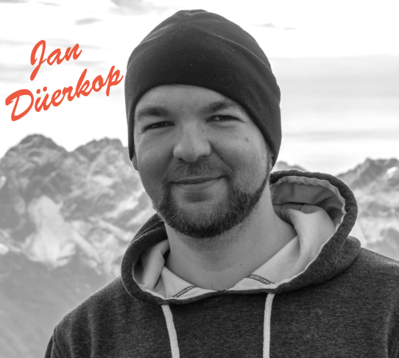 headshot Jan Düerkop smiling with brown beard wearing a dark knit beanie and hoodie against a snow-capped mountain range in the background