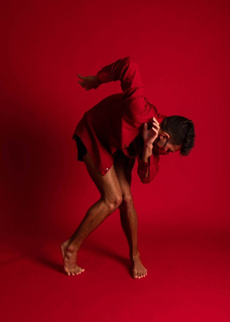Art Photo: Dancer in abstract pose wrapped in red fabric against red background