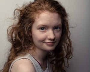 Headshot young woman with red, curly hair and fair skin