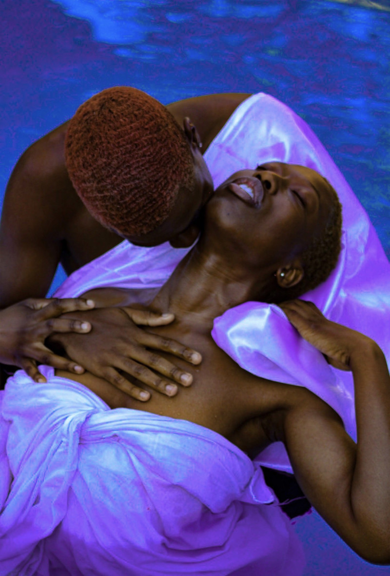 Trevon Davis photo gallery: Couple embracing while lying on purple blanket next to a pool.