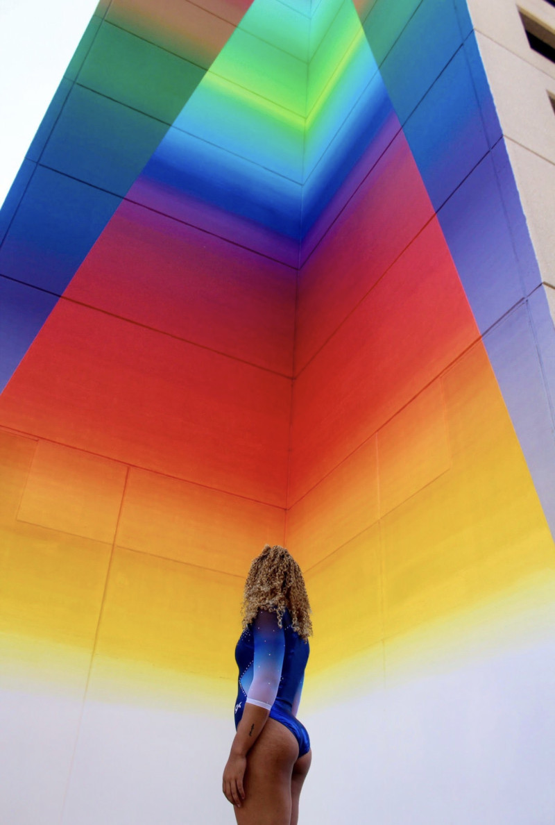 Trevor Davis Photo Gallery: Girk in light vlue gymnast leotardstanding out side looking at rainbow painted on wall.