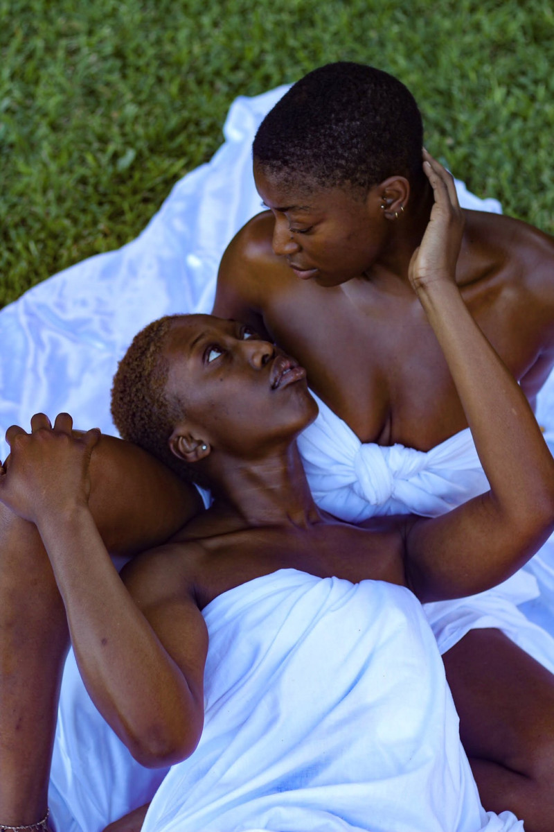 Trevon Davis photo gallery: Couple embracing while lying on white blanket on park grass