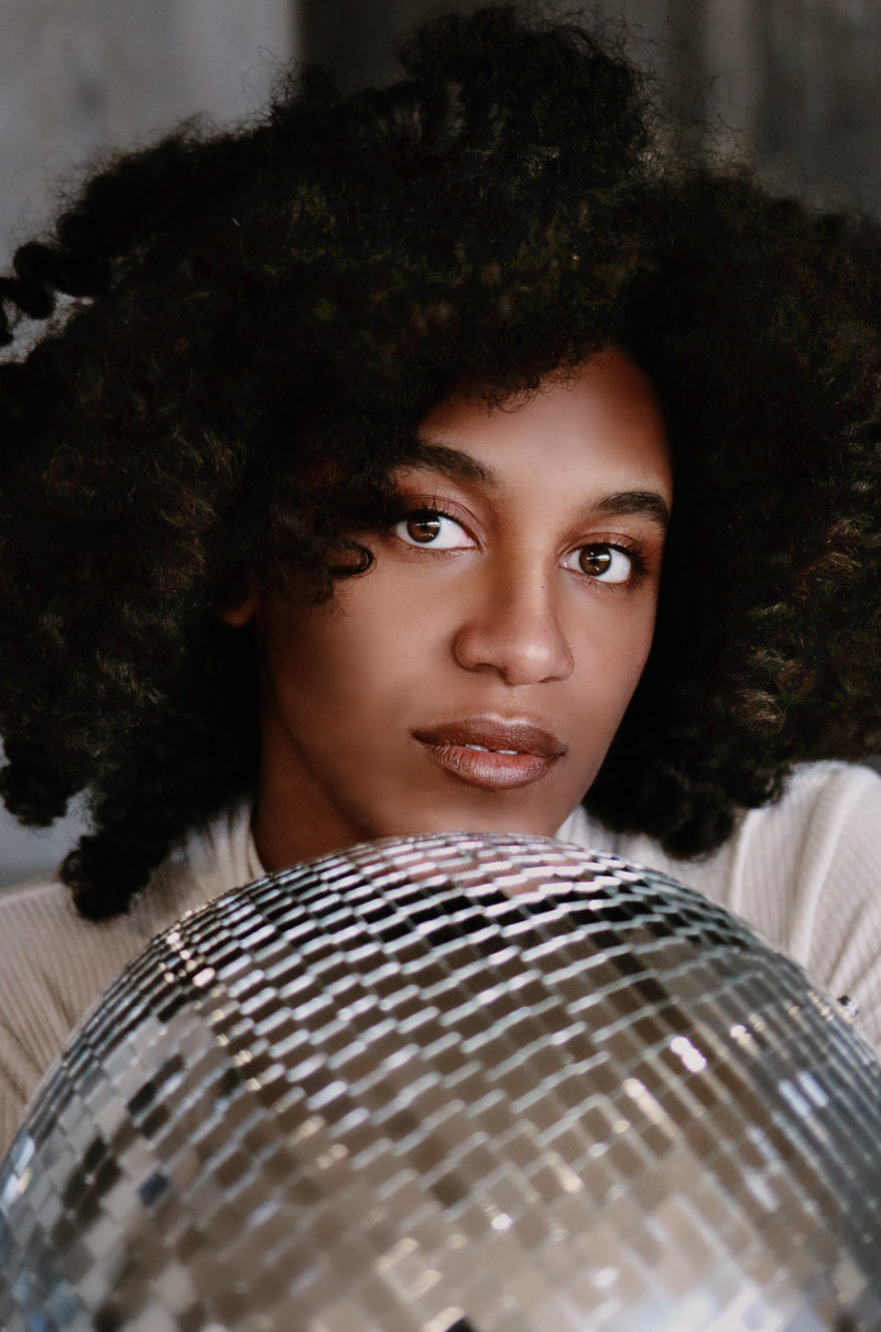 Closeup portrait of a young dark-haired woman holding a silver,glass tiled disco ball in front of her chest
