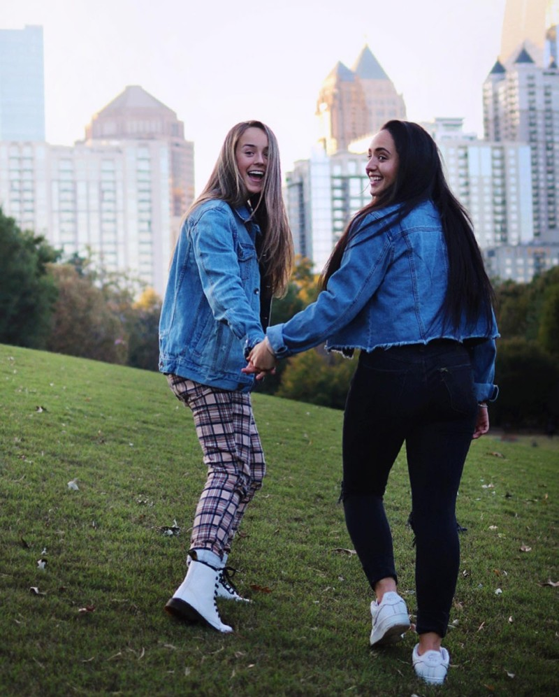 Portrait of 2 young women bothh with waist liength dark hair holding hands looking back over their shoulders as they climg a grassy hill - both wearing slacks and light blue jackets