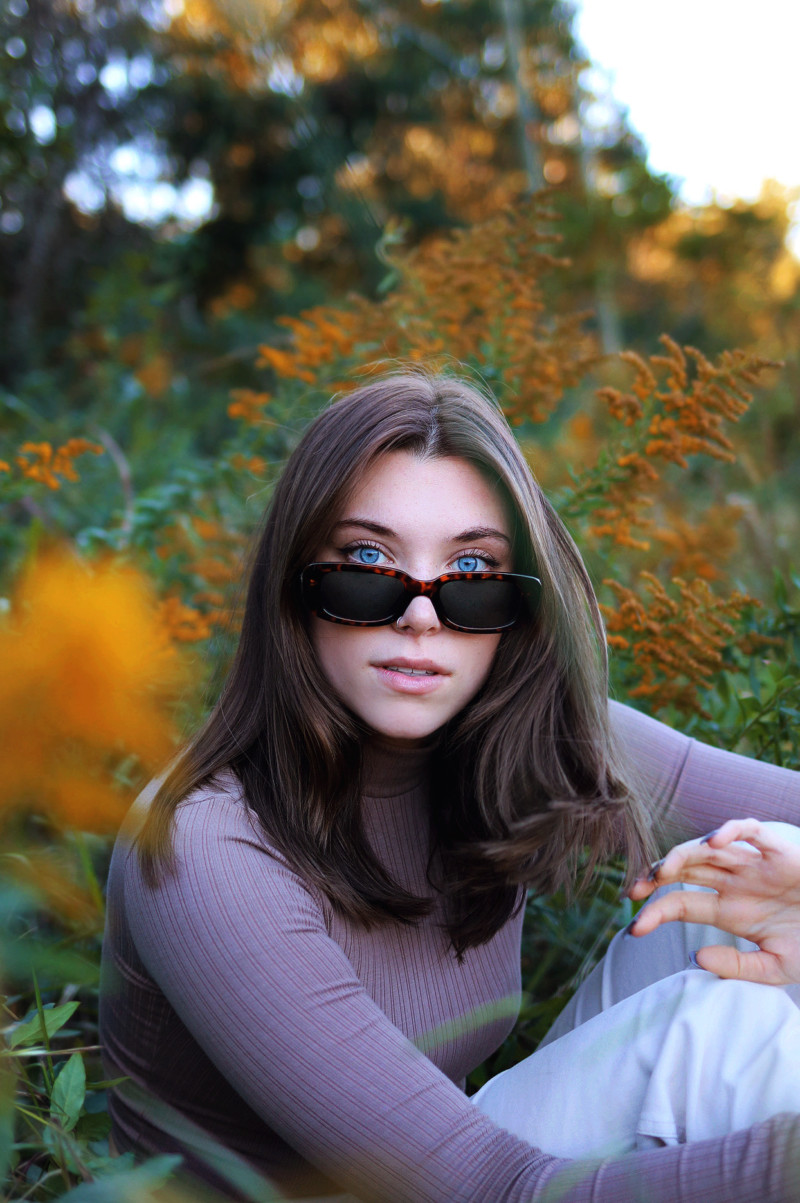 Portrait young woman with long dark hair wearing sunglasses and a lavendar top sitting in frontof orang fall foliage