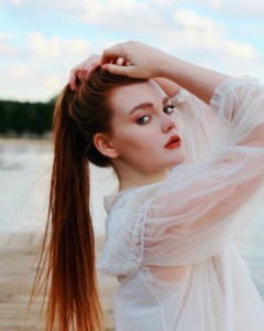 Portrait young woman long dark ponytail 3/4 profile wearing sheer white blouse