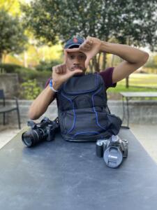 Benjamin Thomlinason: Young man in dark t=shirt and baseball capsitting at picnic table in front of camera