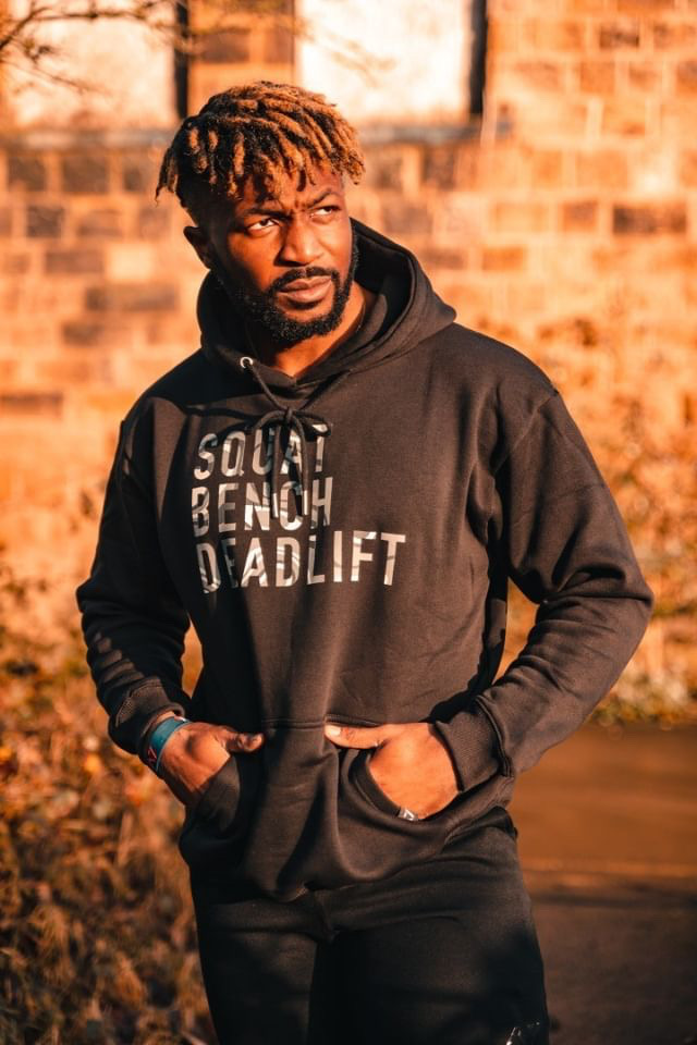 Chris Onuoha: Young man with dark beard and short light brown dreads stands in front of brick wall with hands in dark hoodie pocket