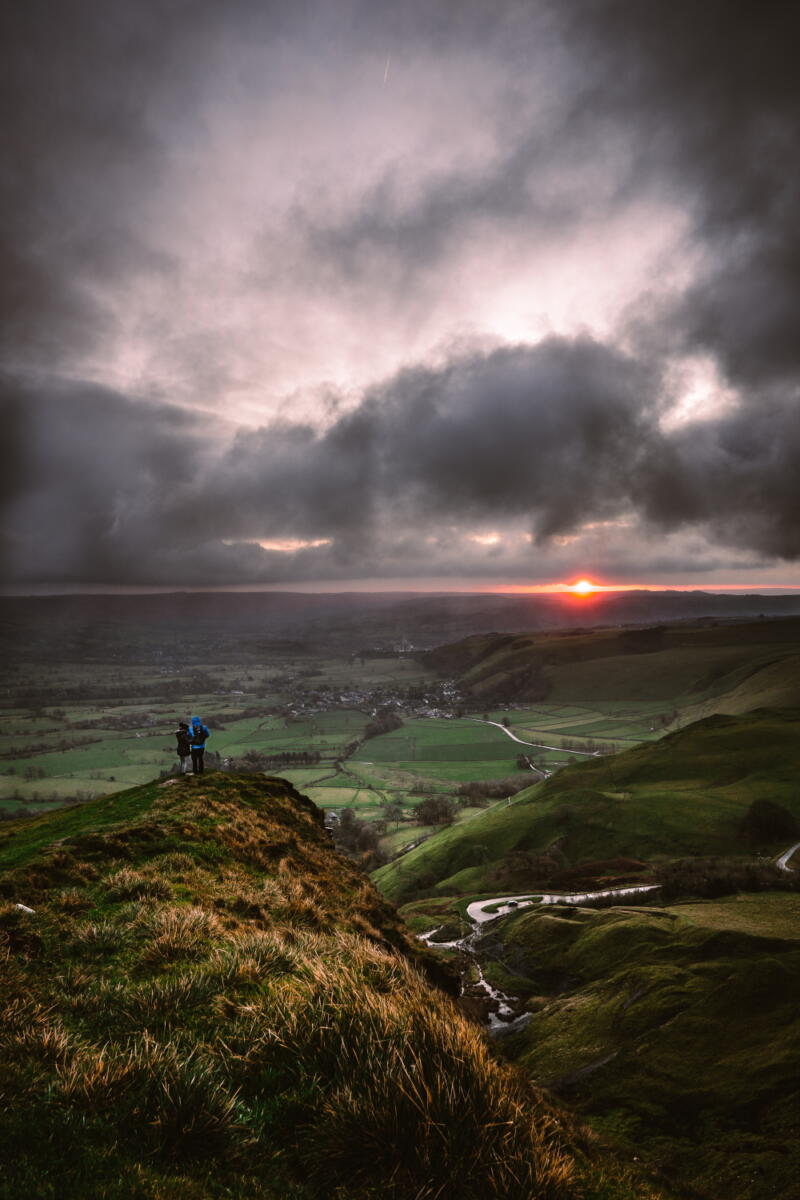 Chris Onuoha: Horizon - Stormy dark clouds and rainstorms on the horizom of an aerial view of a broad green plainwith low hills in the foreground