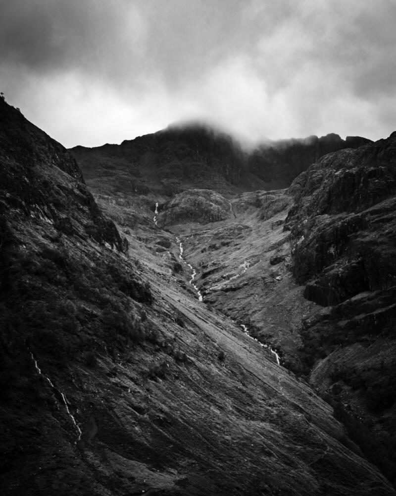 Chris Onuoha: Black and white aerial view of a steep-sided valley with stream under a gray cloud-filled sky