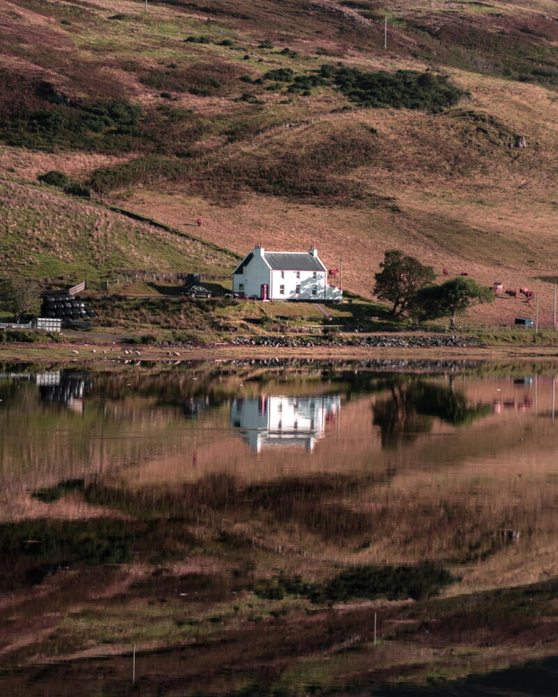 Chris Onuoha: A lonely whte house reflected in a large pond backed by grass covered low hill