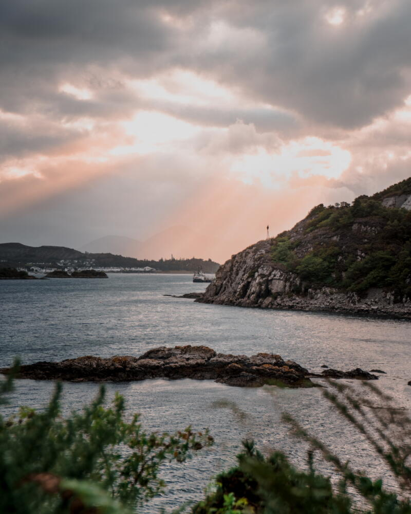 Chris Onuoha: A view over a narrow bay with lowhills at water's edge under a cloudy sky with sunbeams breaking through