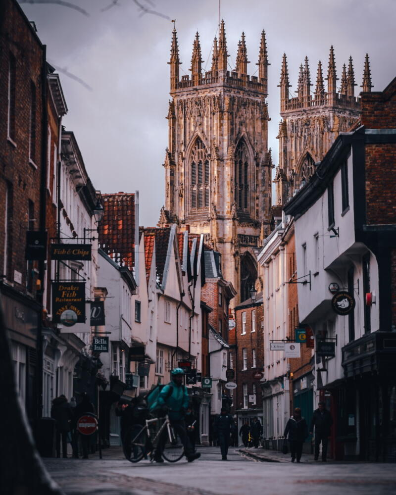 Chris Onuoha: People walking midday on a street in York Minster with Gothic towers rising up at the end of the street