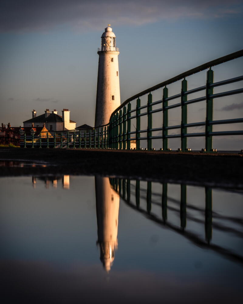 Chris Onuoha: Closeup of dock railing and shadows in water with white Whitley Bay Lighthouse and nearby buildings in the bacground