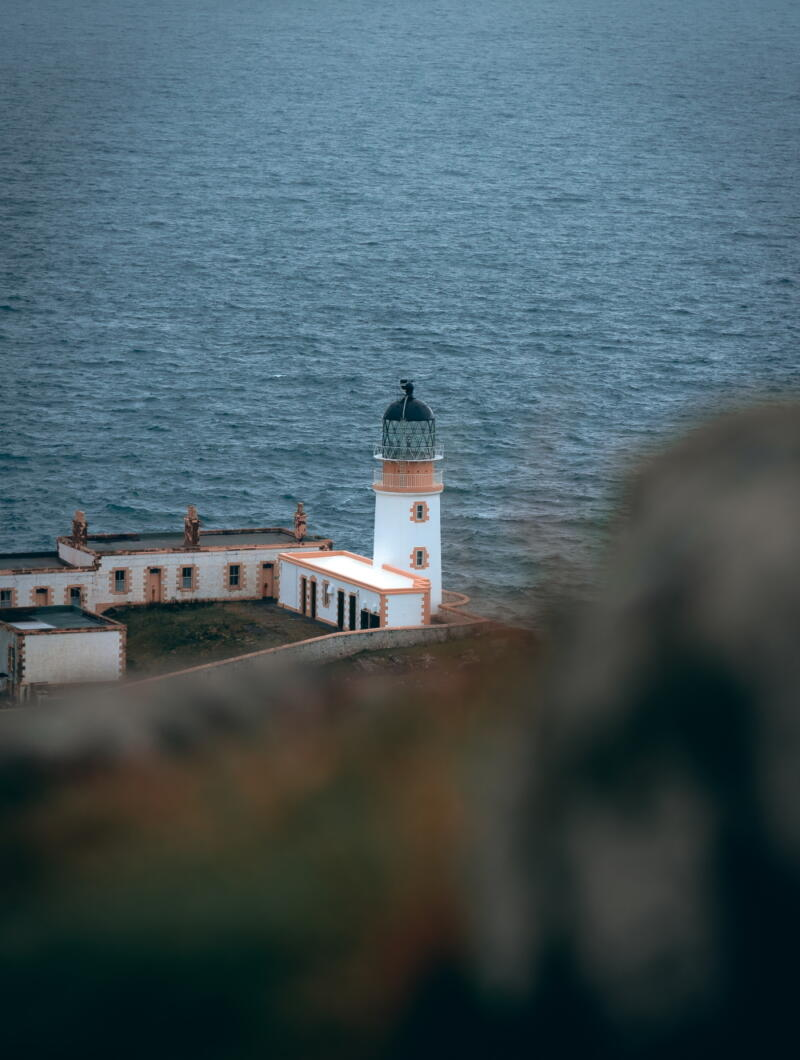 Chris Onuoha: Neist Point - Long view of white lighthouse and lighthouse point buildings with ocean in the background
