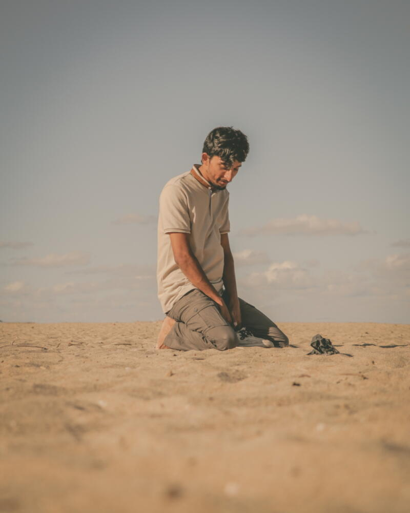 Syed Hamza: Dark-haired man in whitet-shirt and tan pants kneels in sand with hands in lap against gray sky