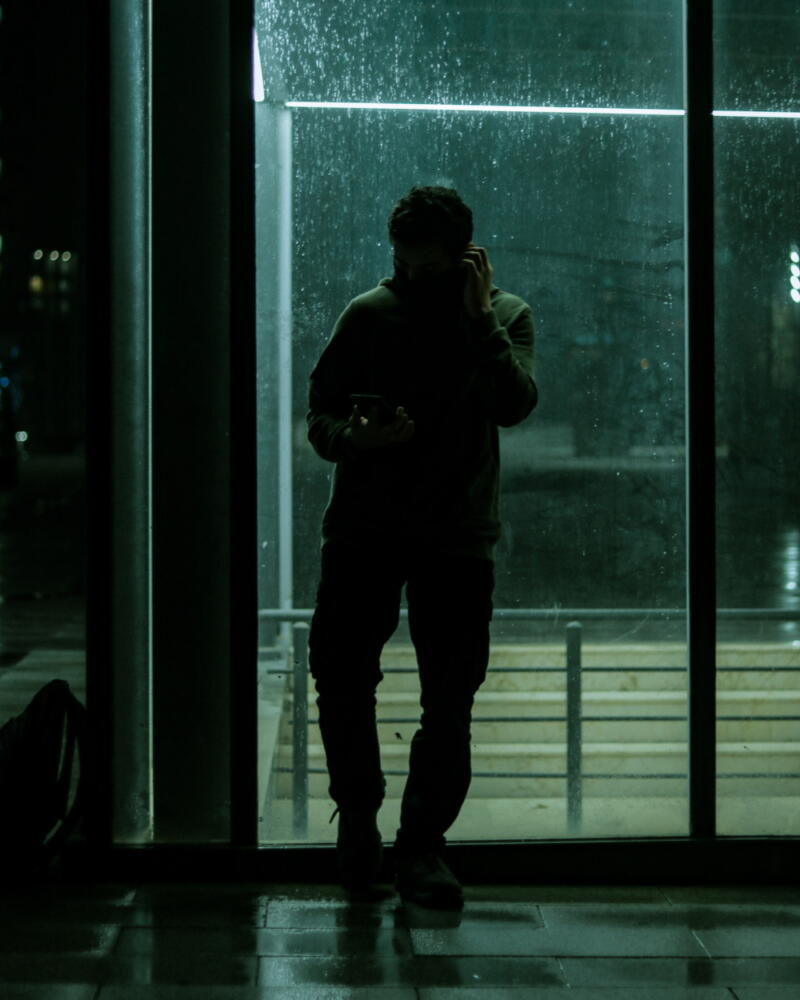 Syed Hamza: Person stands leaning back on a glass door, silhouetted against a grassy sun-lit yard, holding his cellphone up to his ear.