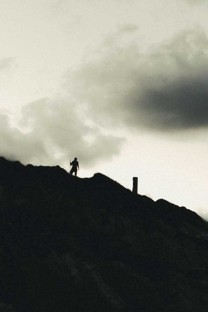 Syed Hamza: Sihouette of a people and and a tallsqure post in the distance standing on a mountain ridge against a cloudy gray sky.
