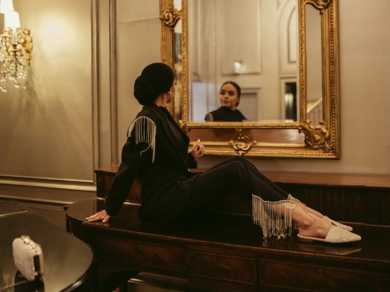 Ali Sardar: Woman n black contemplating self in gilded mirror at Ritz Carton.
