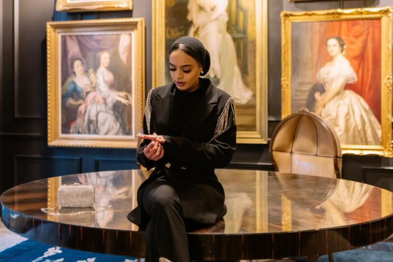 Ali Sardar: Woman in black sitting at black tabl surrounded by clasic art in gilded gold frames.