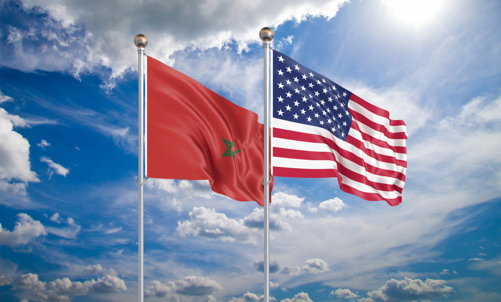 Moroccan and American flags against white clouds in blue sky