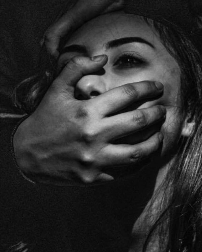 Taylor Mackenzie: close up on woman's face with a hand gripping her mouth