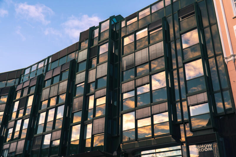 Jan Düerkop: tall building with many windows reflecting the cloudy sky