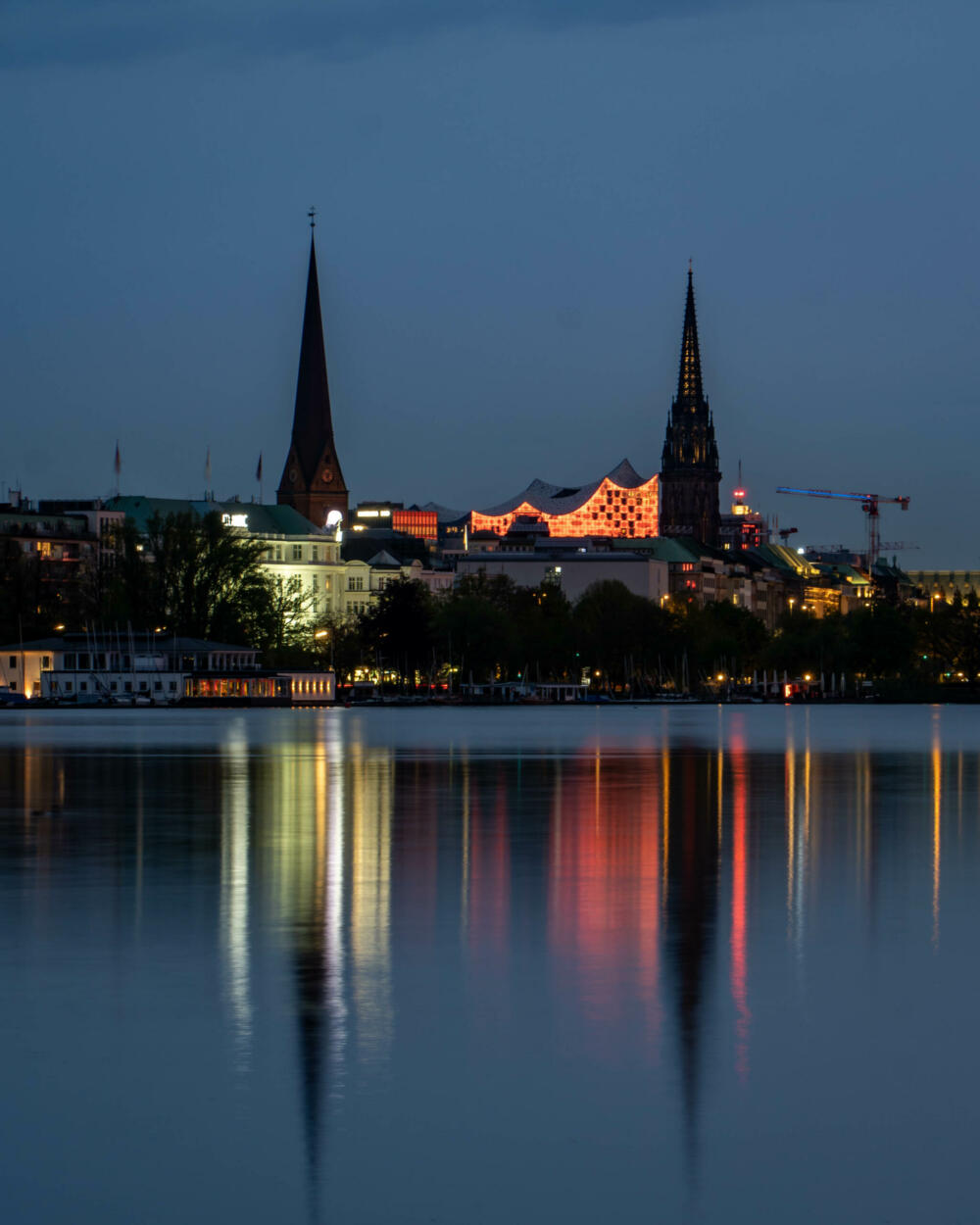 Jan Düerkop: large body of water in front of a city at dawn. Lights from the city reflect of the water.